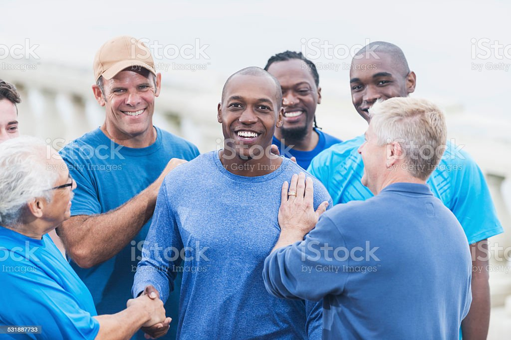 African American man being congratulated by friends stock photo