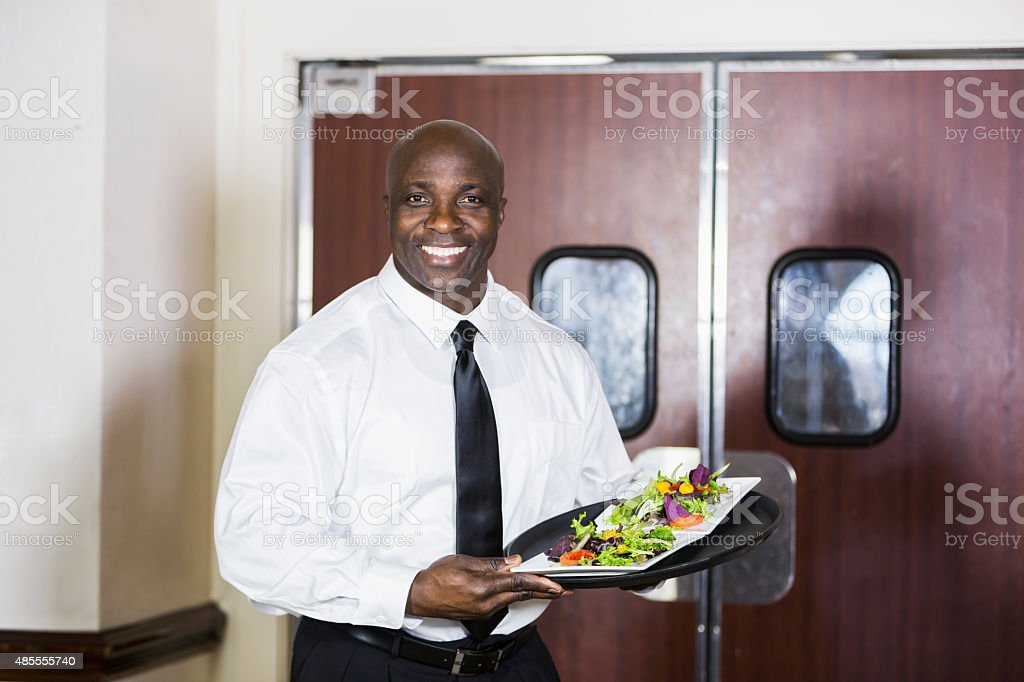 African American man carrying tray of food in restaurant stock photo