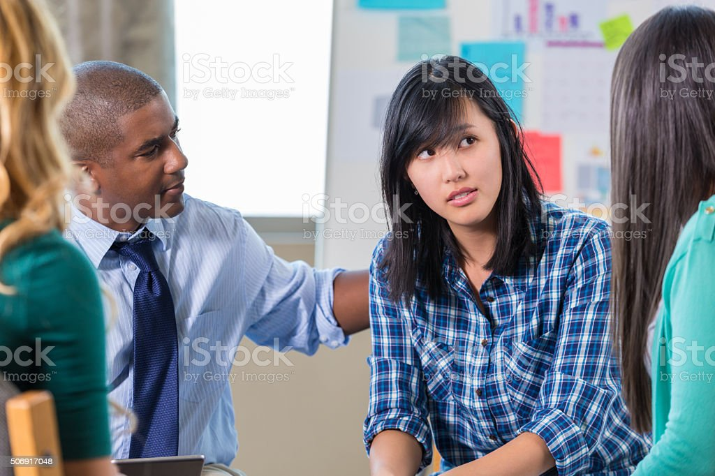 African American man comforts Asian woman in support group therapy stock photo