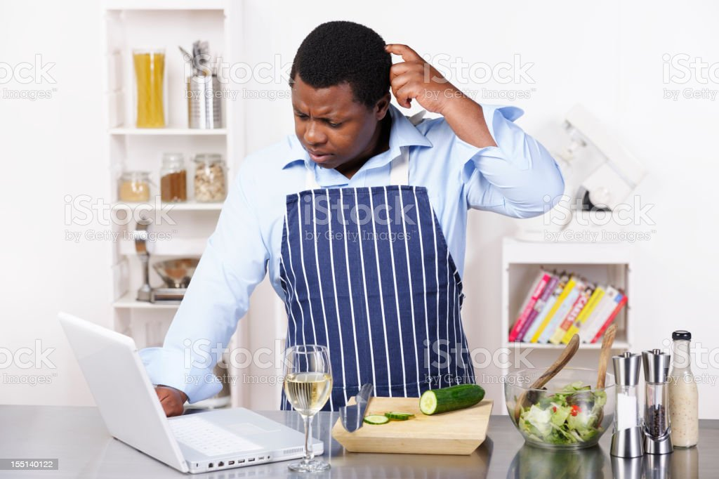 African American Man Contemplating While Using The Computer stock photo