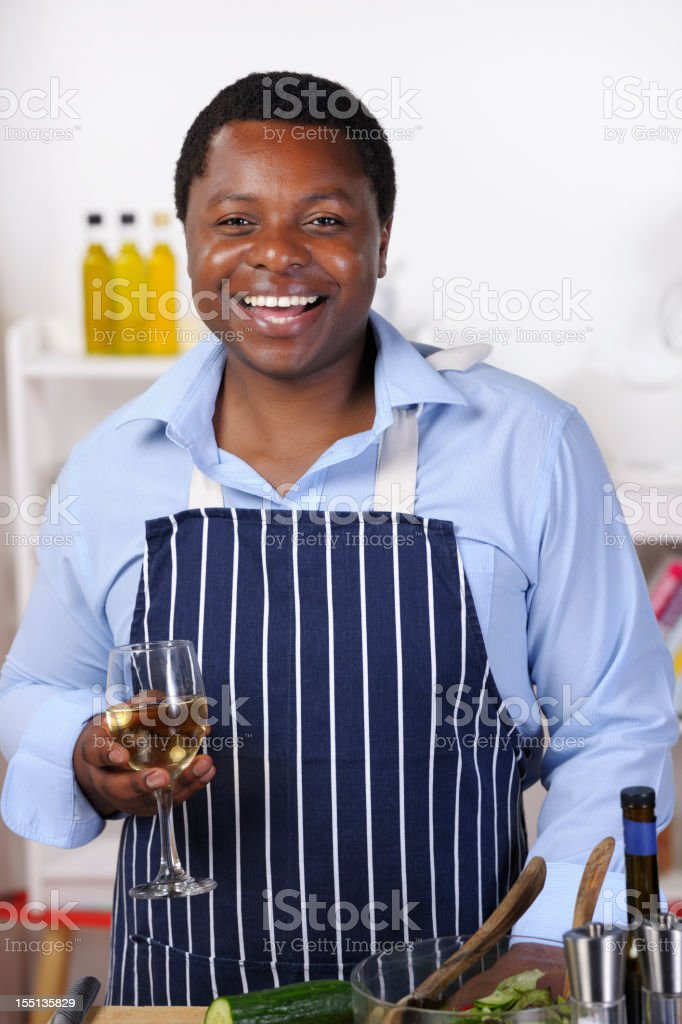 African American Man Enjoying Wine While Preparing Healthy Meal stock photo