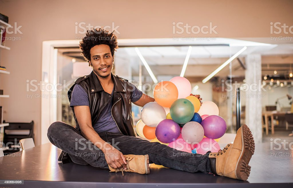 African American man holding balloons while sitting in the office. stock photo