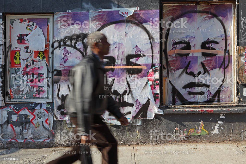 African American man hurries past graffiti covered NYC wall stock photo
