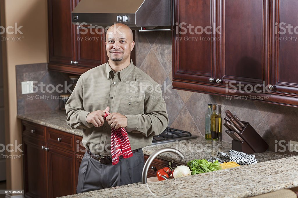 African American man in kitchen wiping hands on dishtowel royalty-free stock photo