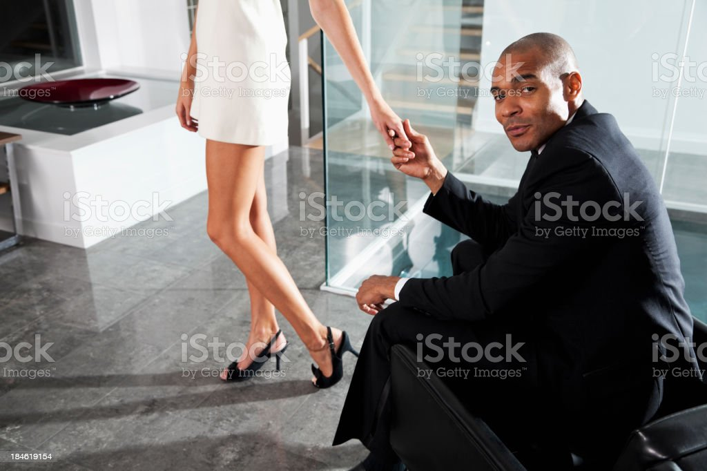African American man in tuxedo holding woman's hand royalty-free stock photo