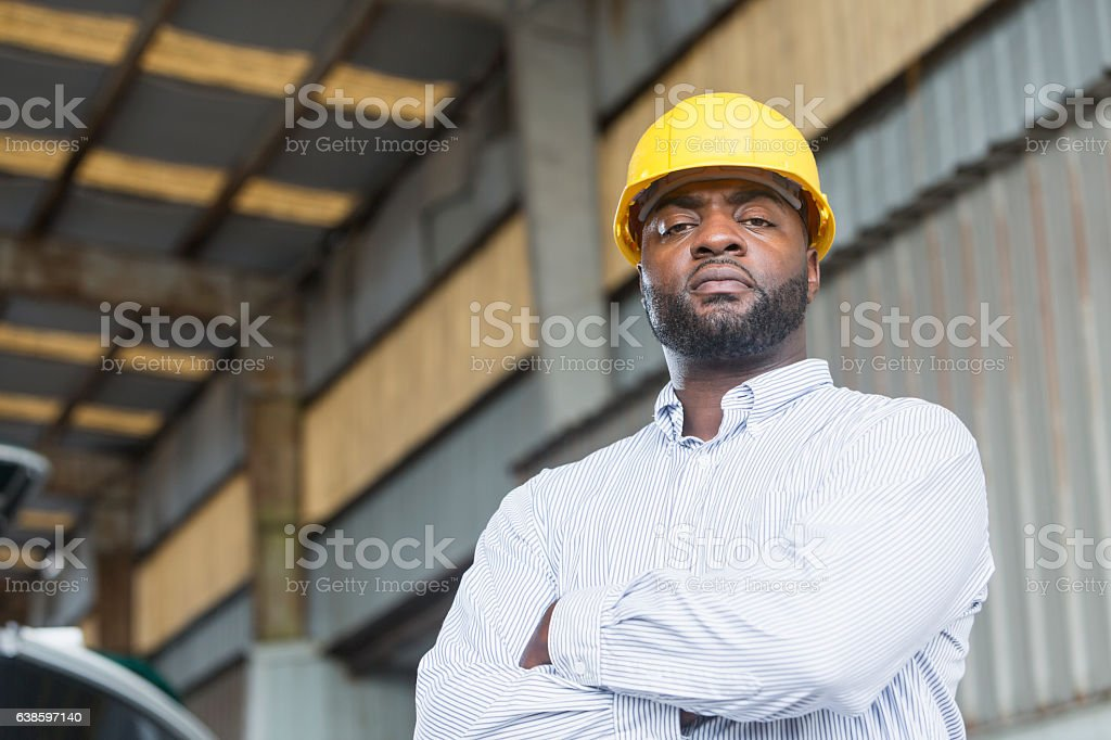 African American man in warehouse wearing hardhat stock photo