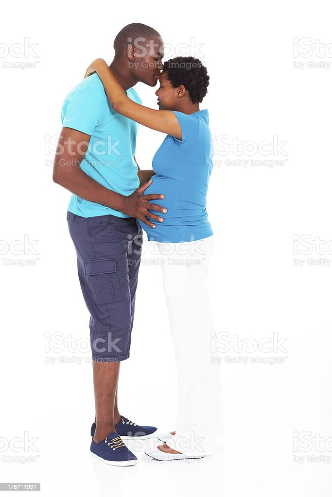 african american man kissing pregnant wife stock photo