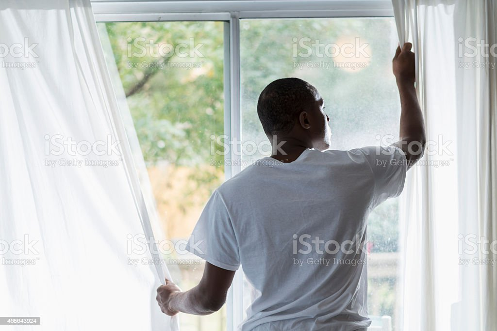 African American man opening curtains on sunny morning stock photo