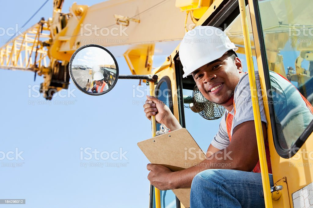 African American man operating a crane stock photo