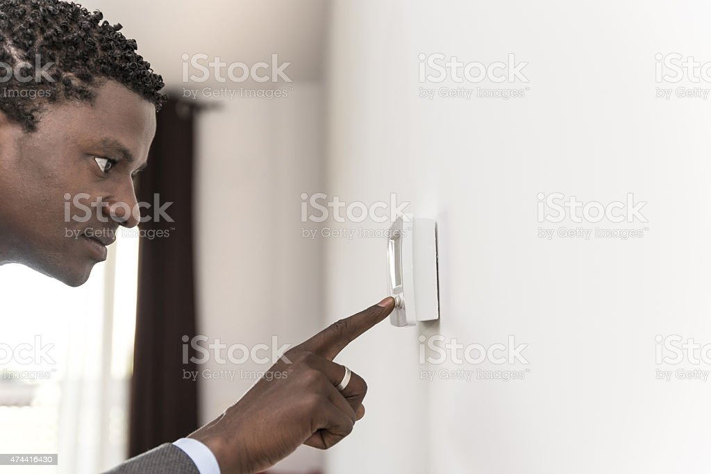 African american man push button digital climate control stock photo