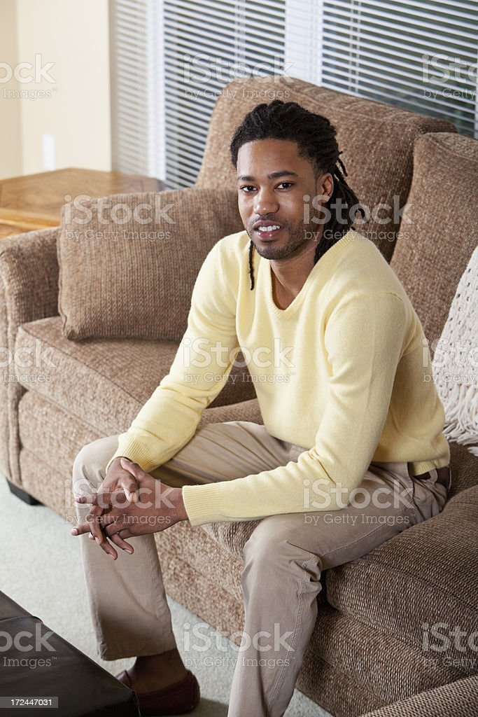 African American man sitting on couch stock photo