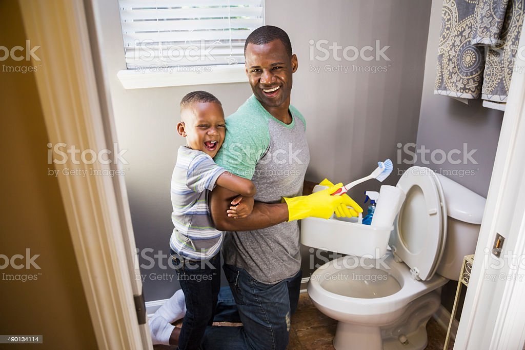 African American man with son, cleaning bathroom toilet stock photo