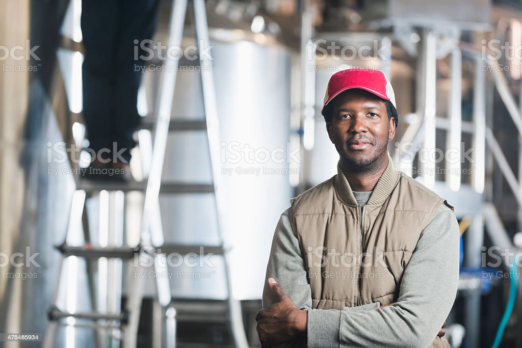 African American man working in microbrewery stock photo