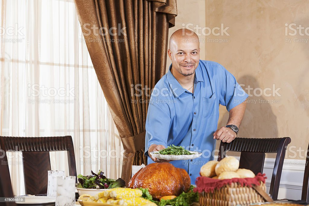 African American middle aged man serving traditional holiday meal stock photo