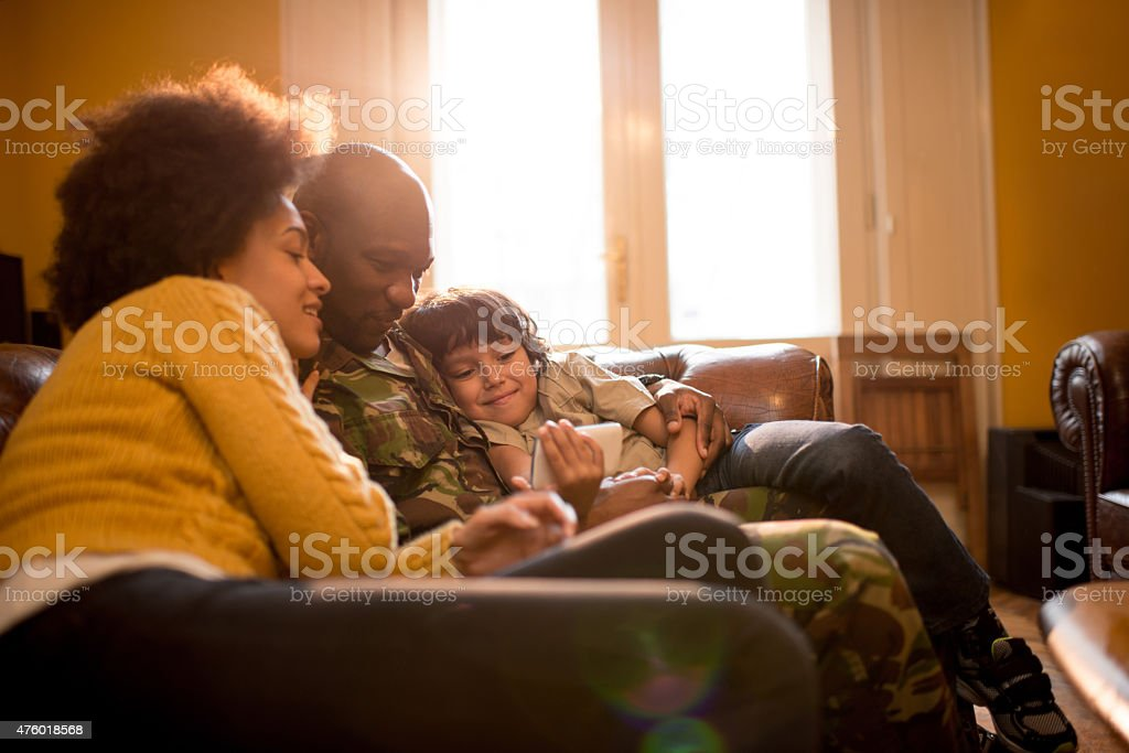 African American military family using cell phone at home. stock photo