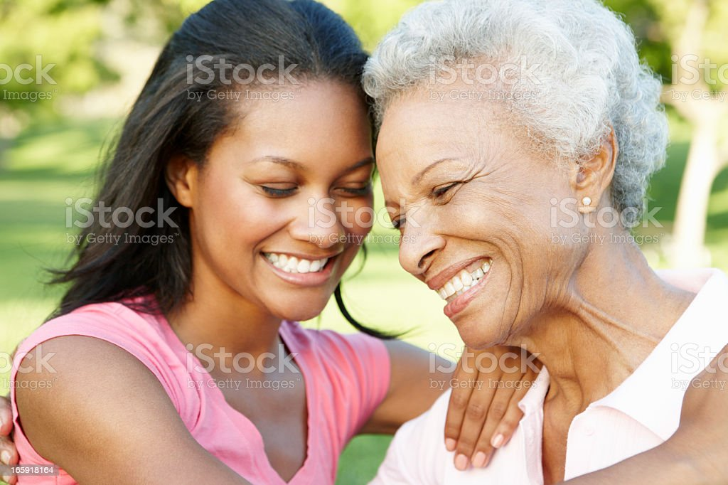 African American Mother And Adult Daughter Relaxing In Park royalty-free stock photo