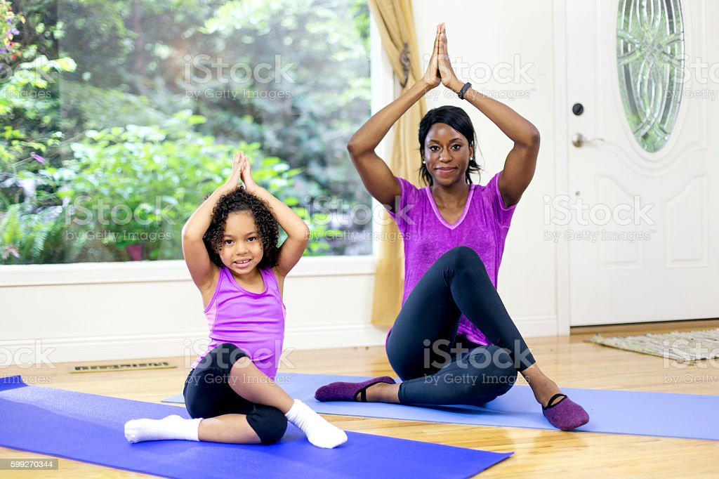 African american mother and daughter doing a yoga pose stock photo