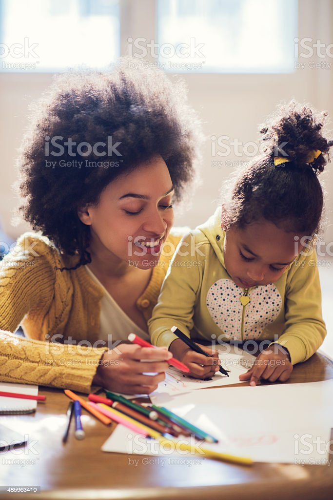 African American mother and daughter enjoying while coloring tog stock photo