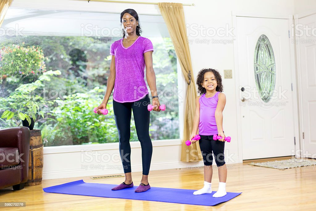 African american mother and daughter lifting weights stock photo