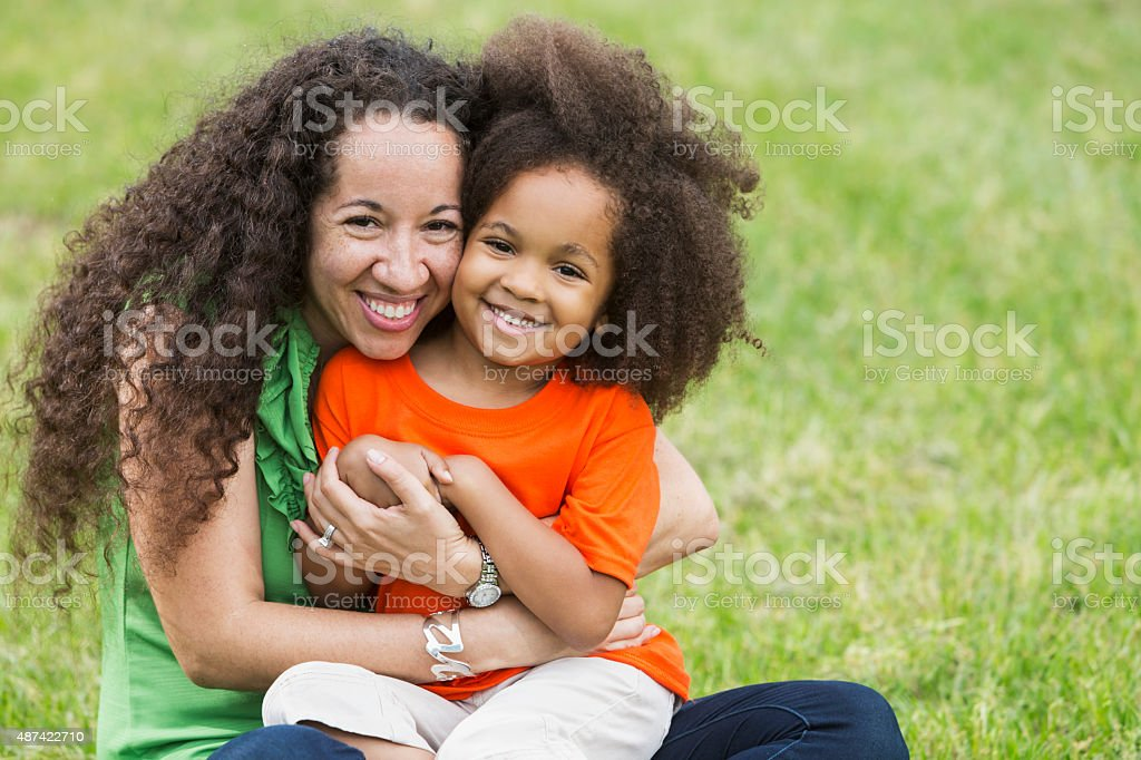 African American mother and daughter outdoors hugging stock photo