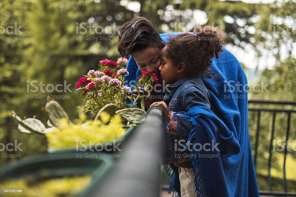African American mother and daughter smelling flowers on a terrace. stock photo