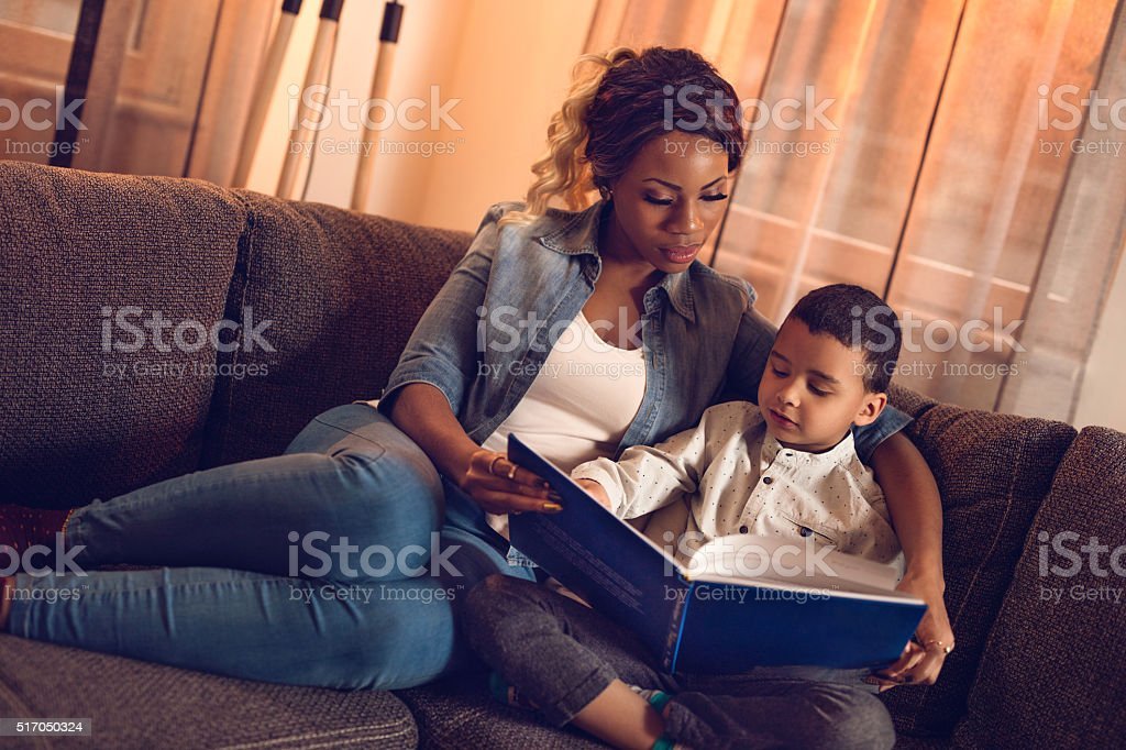 African American mother and son reading book at home. stock photo
