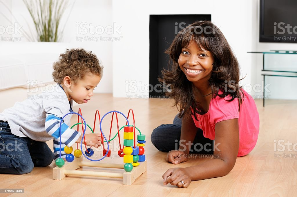 African American Mother And Toddler Enjoying Playtime In The Lounge stock photo
