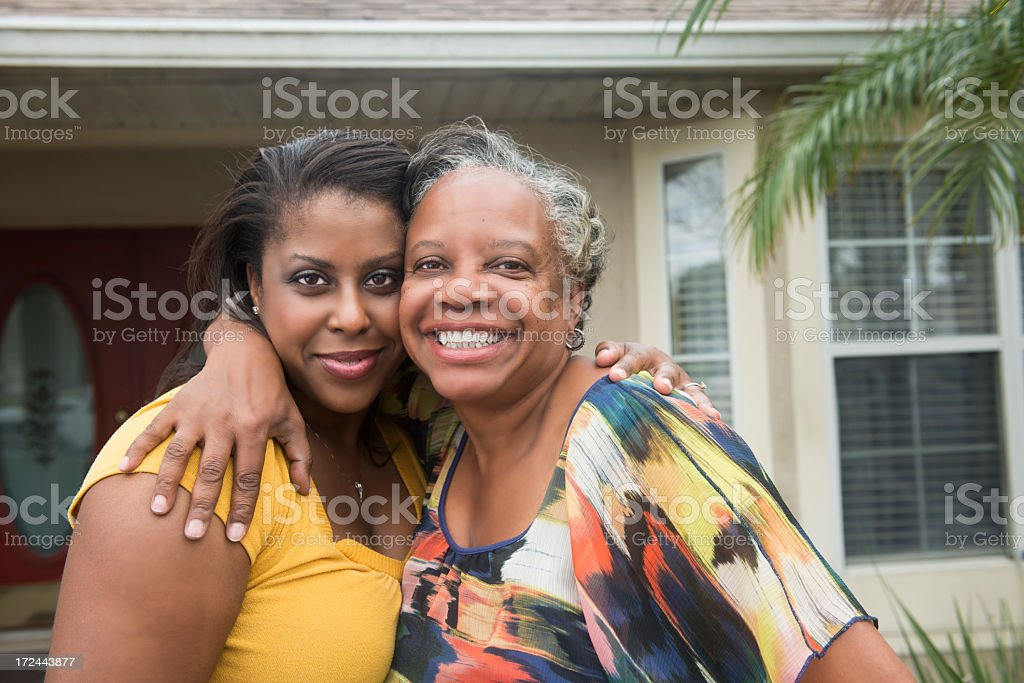African American Mother & Daughter Smiling In Front of Home stock photo