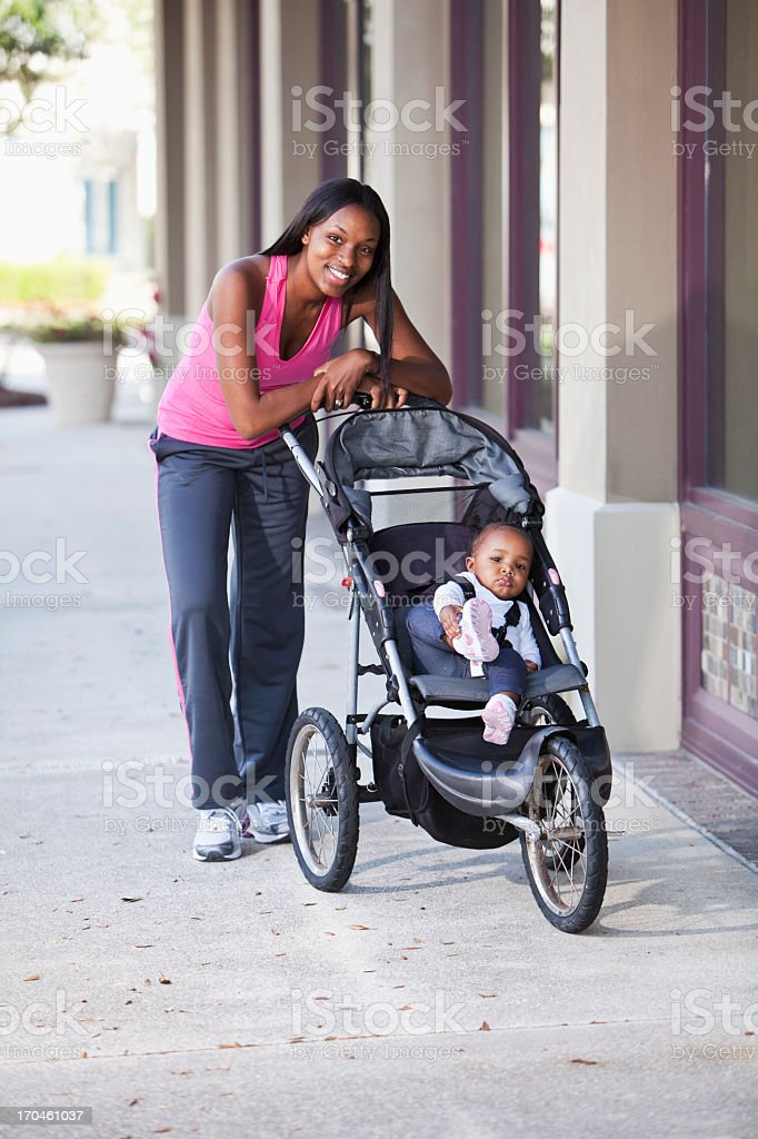 African American mother pushing baby stroller on sidewalk stock photo