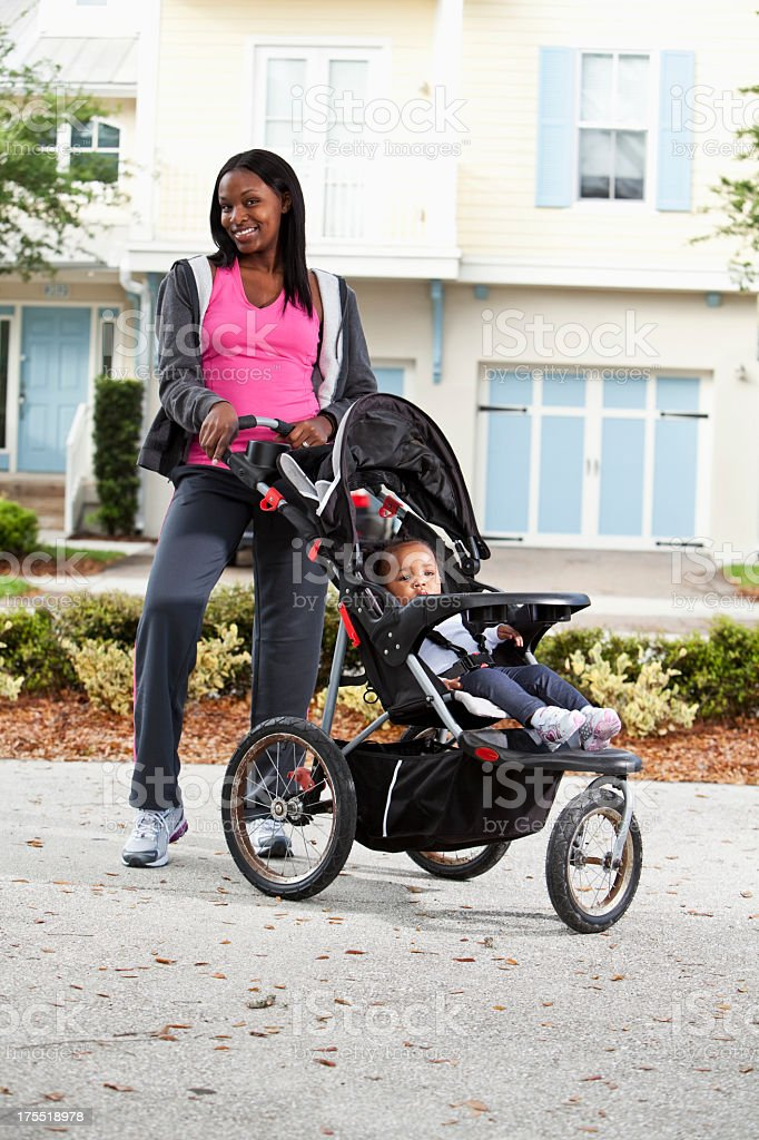 African American mother with baby in jogging stroller stock photo