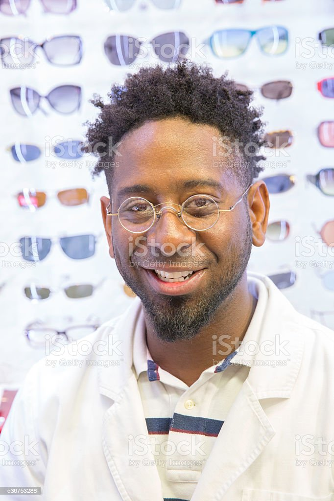 African American optometrist standing in from of eye glass display stock photo