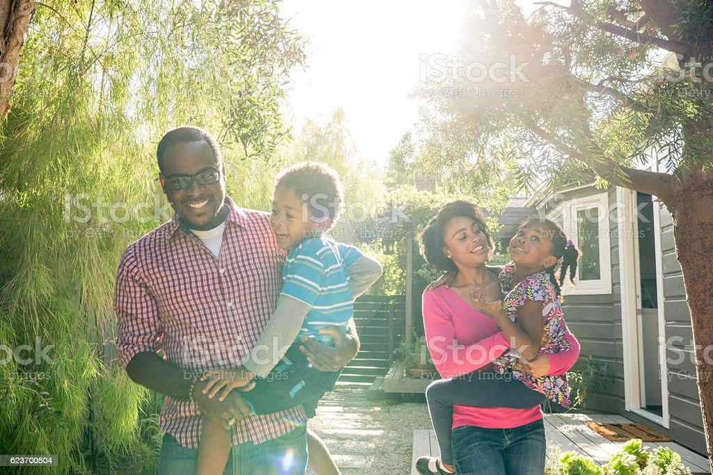 African American parents in garden carrying their children stock photo