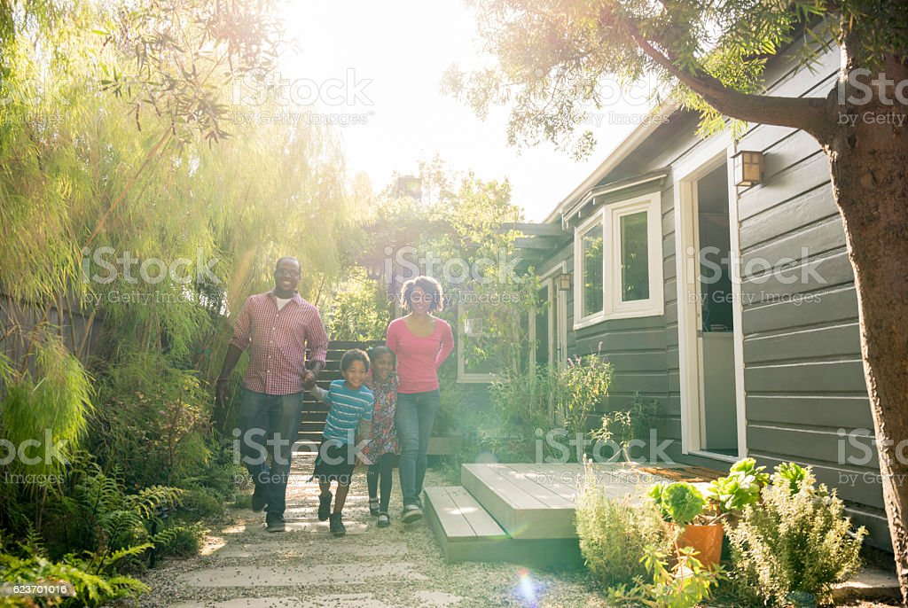 African American parents with two children walking in garden stock photo