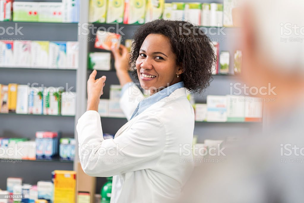 African American pharmacist serving customer in pharmacy. stock photo