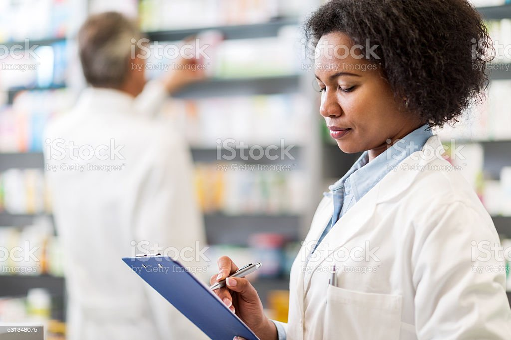 African American pharmacist writing. stock photo