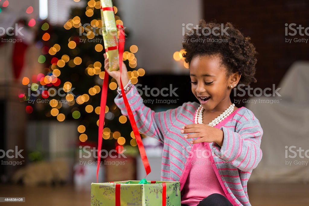 African American preschool girl opening Christmas present stock photo