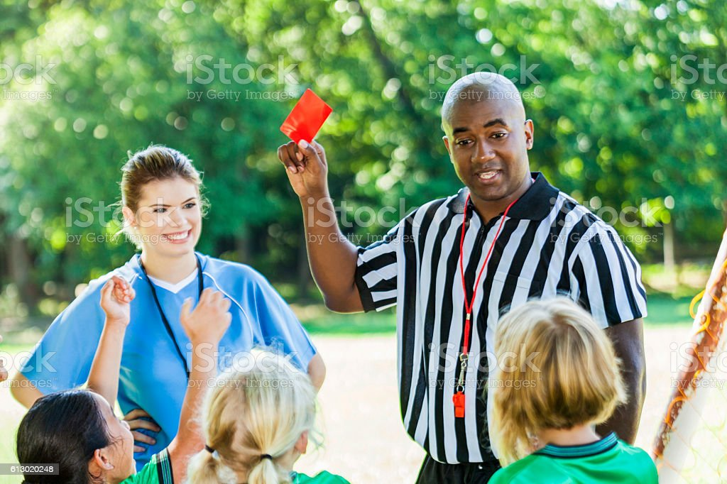 African American referee explains penalty to youth soccer players stock photo