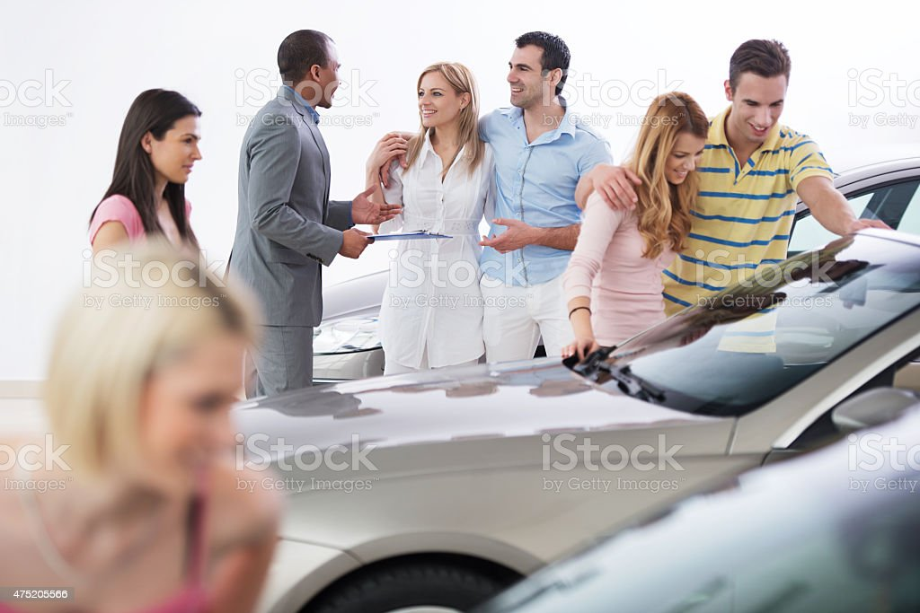 African American salesperson and his customers in a showroom. stock photo