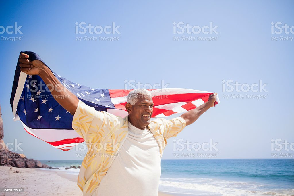 African American Senior Carrying USA Flag on the Beach stock photo