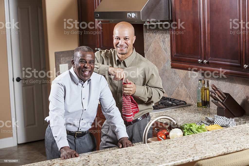 African American senior man and adult son in kitchen stock photo
