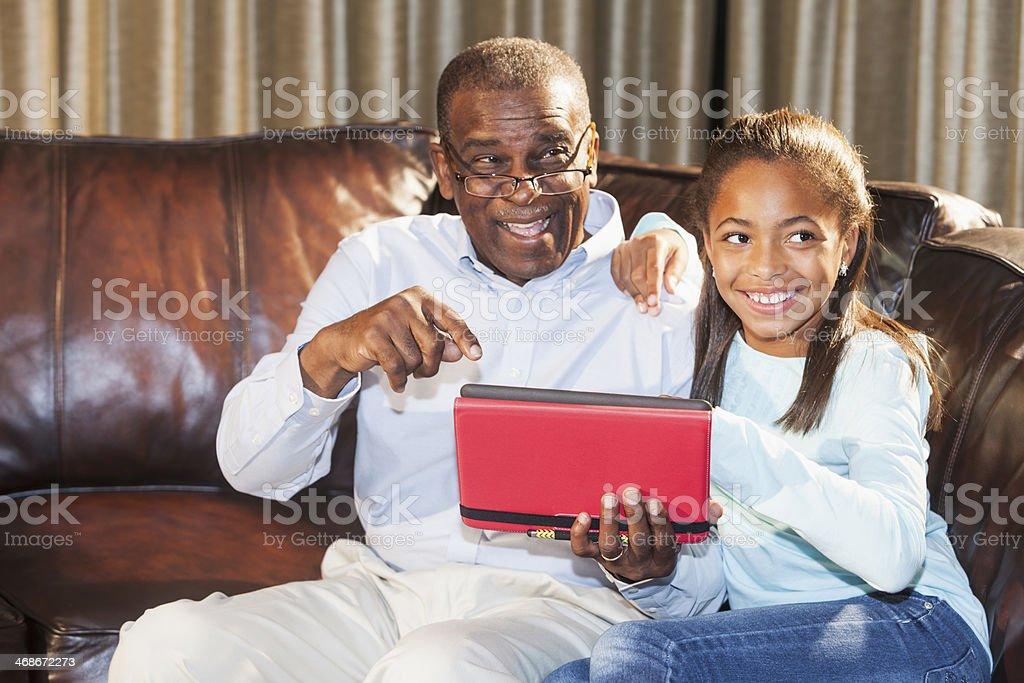 African American senior man with grandchild using digital tablet stock photo