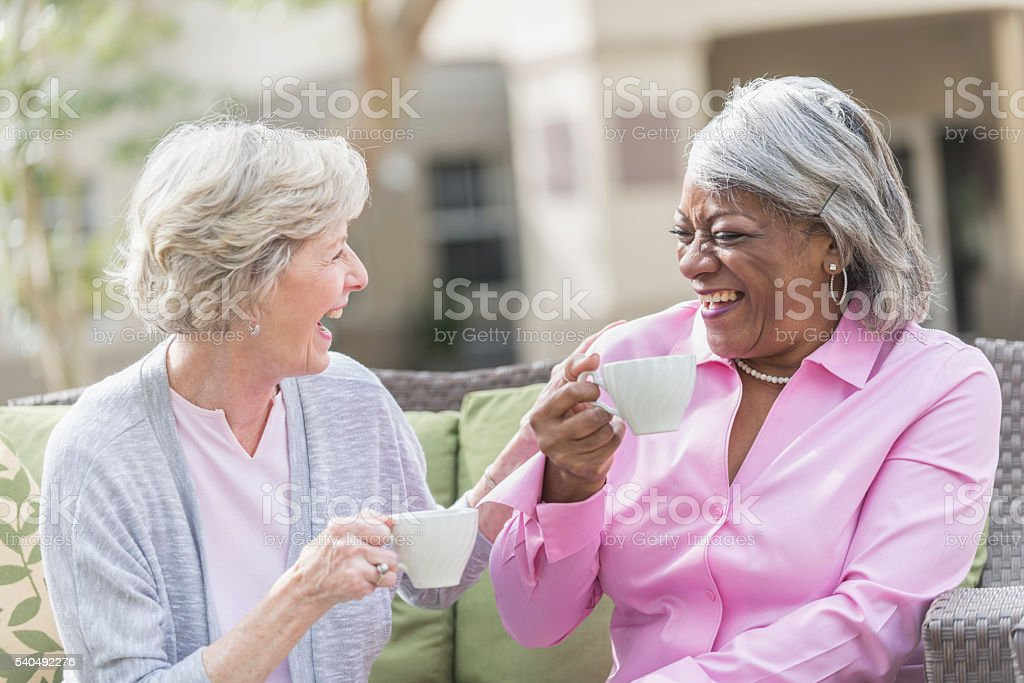 African American senior woman, friend talking over tea stock photo