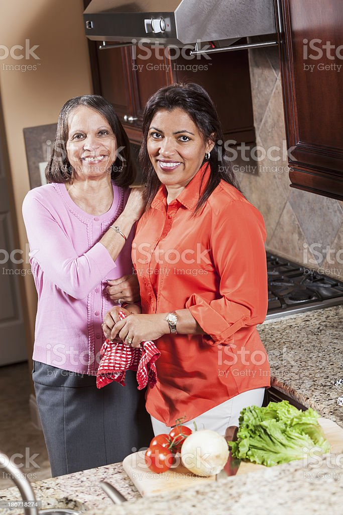 African American senior woman with adult daughter in kitchen stock photo