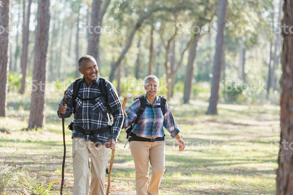 African American seniors hiking through woods stock photo
