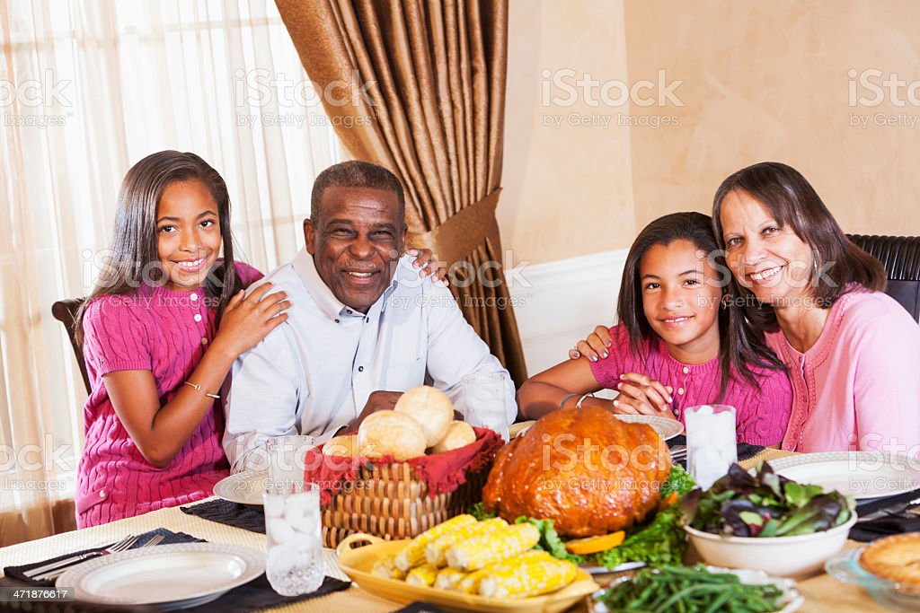 African American seniors with grandchilden enjoying a holiday dinner stock photo