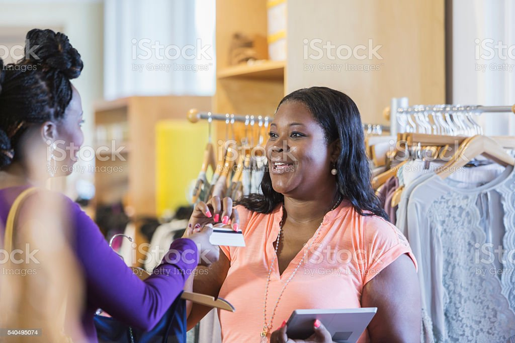 African American shopper and saleswoman in store stock photo
