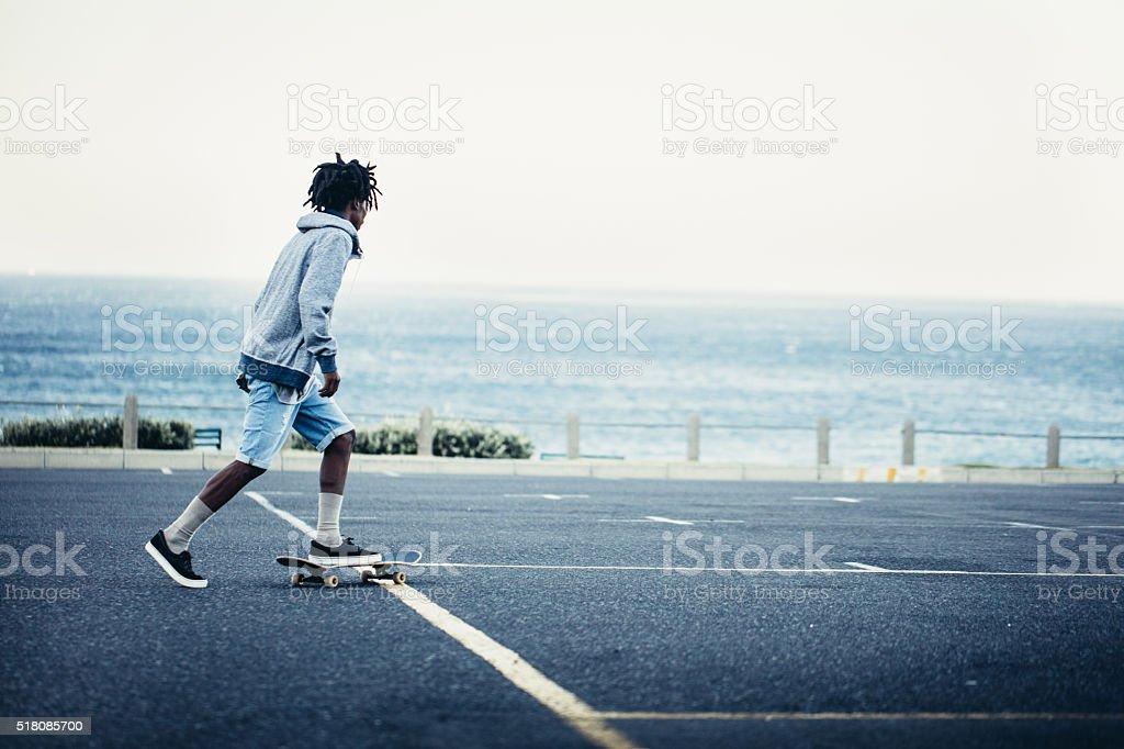 African American skateboarding in seaside parking lot stock photo
