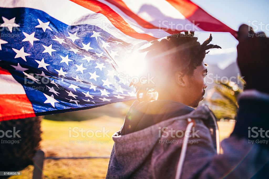African American Skater Holding American Flag During Sunset stock photo