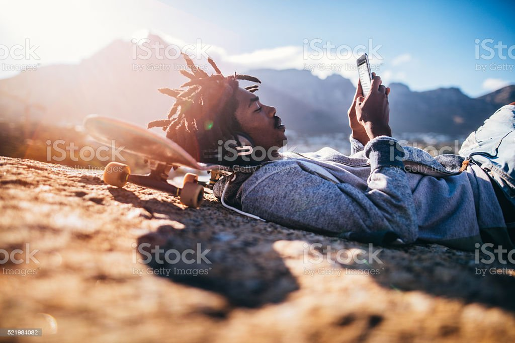 African American Skater Resting and Looking at Smartphone at Sea stock photo