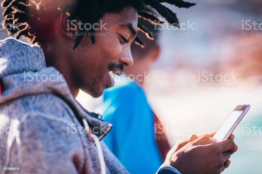 African American Skater Sitting and Looking at Smartphone Outsid stock photo